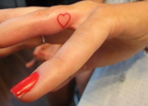 tiny heart outline finger tattoo