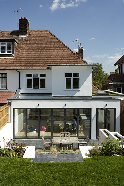 CONTEMPORARY HOUSE RENOVATION AND EXTENSION CROUCH END NORTH LONDON  New aluminium sliding folding doors span the full width of the garden extension and a structural glass fixed rooflight also spanning across the extension both combine to maximise daylight within the newly created kitchen and dining area connecting the space seamlessly to the garden when doors are opened fully.  London Architects and Interior Designers www.crawfordpartnership.co.uk