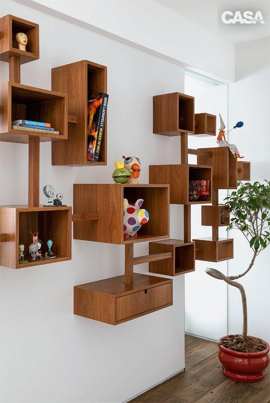 urpresa para quem chega ao apartamento: no hall, a estante Árbol (Llussá Marcenaria) exibe as coleções dos moradores.
