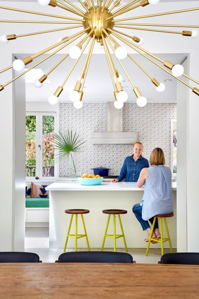 Clean, white midcentury kitchen with colorful accents, gold light fixture