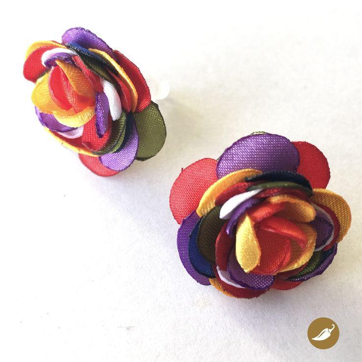 En esta joya, Nini del Rìo, se inspira en uno de los rasgos más característicos de la Fiesta de la Tirana: el Color. El color colma la pampa del Tamarugal, a través de las máscaras, cintas, trajes, sombreros y flores. Las telas siempre son brillantes, por ello Nini utiliza satín para crear esta línea inspirada en la mayor apoteosis coreográfica de Chile. Nini del Rio se decide por la policromía y la plasma en estos aros de tope, que como los bailes del norte grande abrazan distintos tonos…
