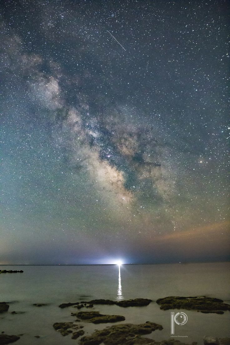 A fishing boat made an extra star floating at the edge of the horizon so close to the sky!