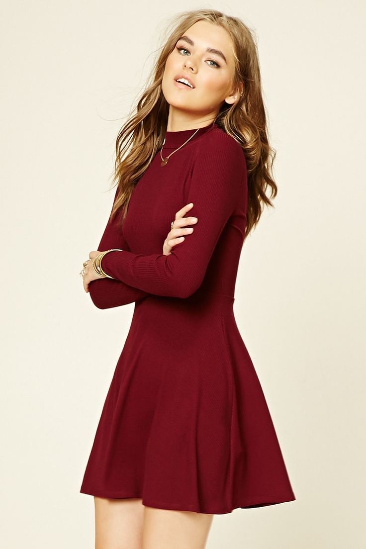 A ribbed knit skater dress with a mock neckline, a self-tie cutout back, and long sleeves.