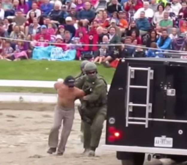 RCMP Entertain Children By Wielding Assault Rifles And Dragging A Shirtless Man Through A Car Window. Note that the man is shirtless, always the tell-tale sign of a criminal.