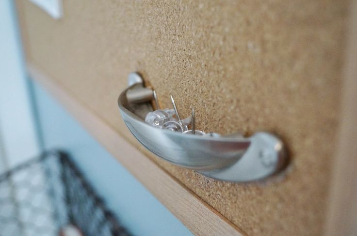 What a great idea: use a drawer pull to hold push pins on the cork board. Yes!