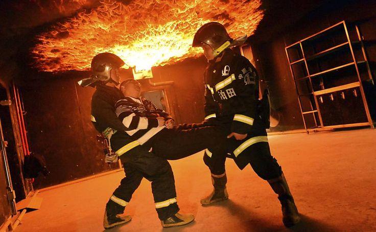 Equipe de resgate simula um salvamento durante incêndio programado em um campo petrolífero durante treinamento de combate a incêndios em Puyang, na China  Foto:China Daily/Reuters