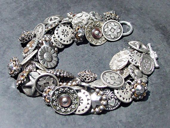 This button bracelet has an eclectic mix of silver metal and pewter buttons dating from the late Victorian era to modern day. There are fifty two buttons on this bracelet with designs and patterns of geometric; Celtic knots; flowers; paisleys; Aztec; intricate steel balls with open cut-work and a tiny amount of brass filigree; a beautiful old round steel-cut; steel-cut stars; heart with flower and several with mother of pearl and abalone set in patterned silver metal.