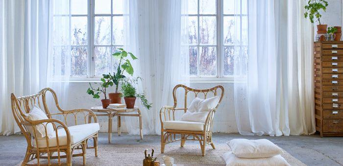 Ein helles Wohnzimmer mit einer Schicht lichtdurchlässiger Gardinen, die Tageslicht filtern, einer Schicht, die Spiegelungen auf Bildschirmen verhindert, und einer dicken weißen Gardine für mehr Privatsphäre.