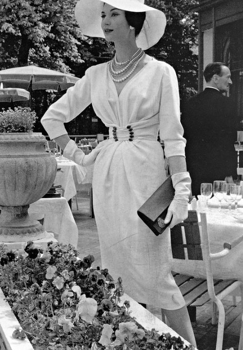 Simone d'Aillencourt in white crépe dress with softly draped bodice cinched by buckled waistband by Nina Ricci, 1957