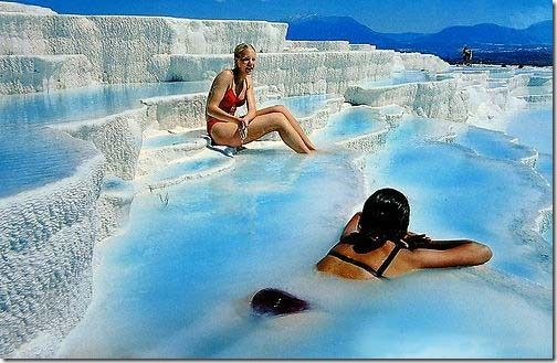 """Pamukkale Turkey by the Aegean Sea. The name Pamukkale literally means """"cotton castle"""". At the top of the hill, you can see the Turkish country side for miles and there is a bathing pool (it cost about $10 and is worth every penny!), the water is hot and fizzy like soda. But the best part is that the pool is located over the ruined temple of Apollo and you swim over tumbled-down marble pillars."""