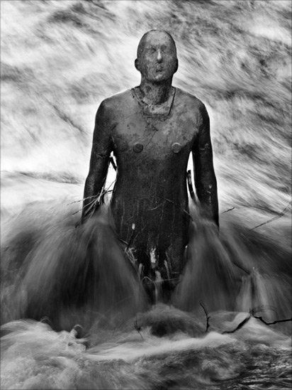Turbulent streams flow past Antony Gormley sculpture following heavy rainfall, Water of Leith, Edinburgh