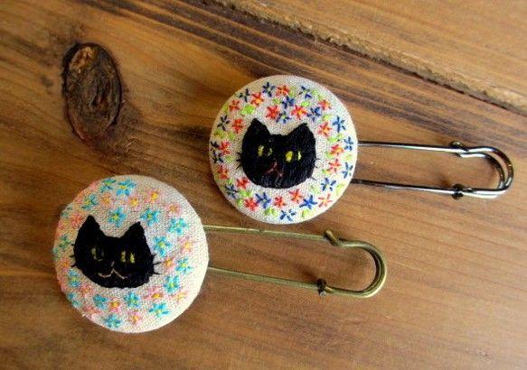 ネコの刺繍のブローチです。クロネコの刺繍ブローチです。周囲のお花模様が違っており、左は空色&ピンク、ミグはブルー&レッドになります。ネコの表情も違いますので、...|ハンドメイド、手作り、手仕事品の通販・販売・購入ならCreema。