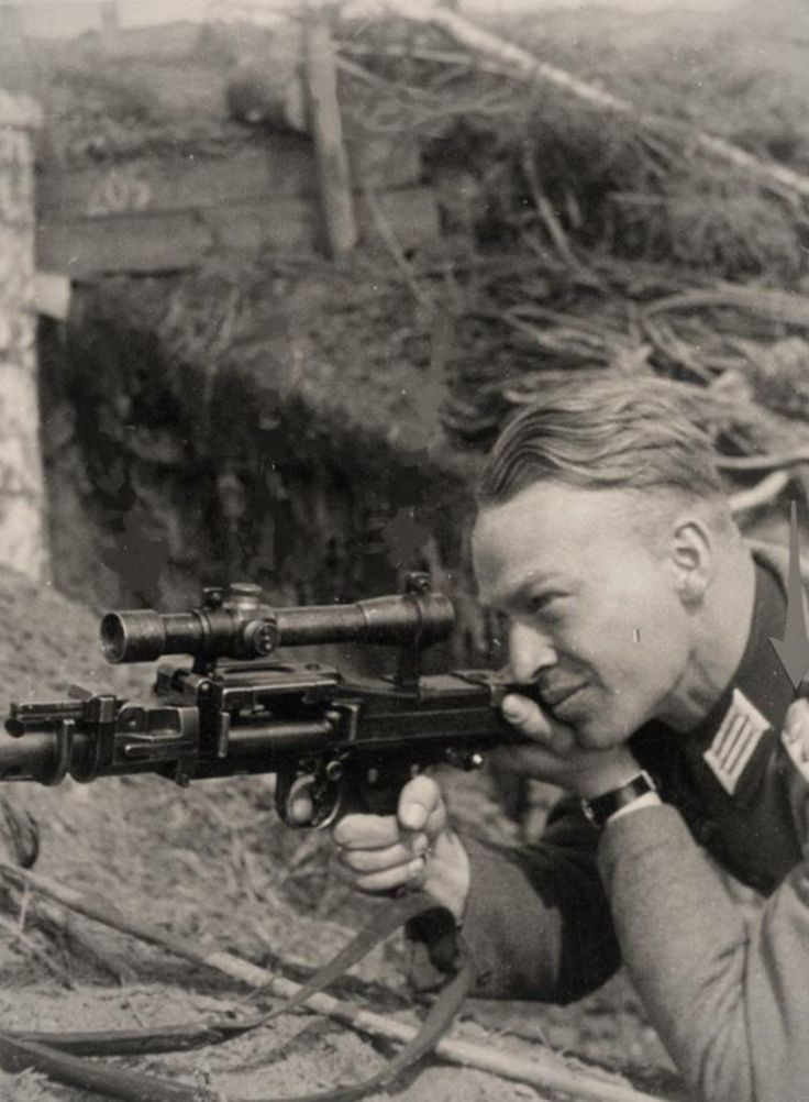 A German soldier taking practice aim with a telescopic sight mounted on an unloaded MG34 machine gun, via Süße Dunkelheit