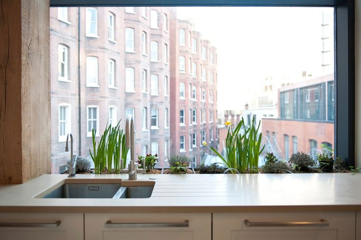 Window box incorporated into the kitchen work tops to deal with low window height.