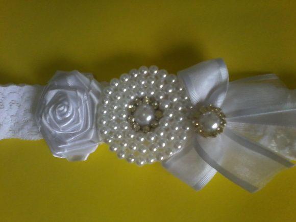 Faixa em renda branca (resistente) com elastano. Detalhe: Rosa em cetim branco, laço branco de cetim e organza e mandala com perola branca. Fazemos em outras cores sob consulta.
