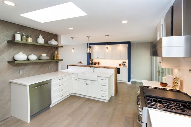 Think beyond traditional finishes when choosing a hardwood floor for your kitchen. Wide-plank engineered wood floors with a slightly grayish hue lend a casual, rustic feel to this kitchen. An angled wood feature wall with open shelving adds additional texture and visual interest.