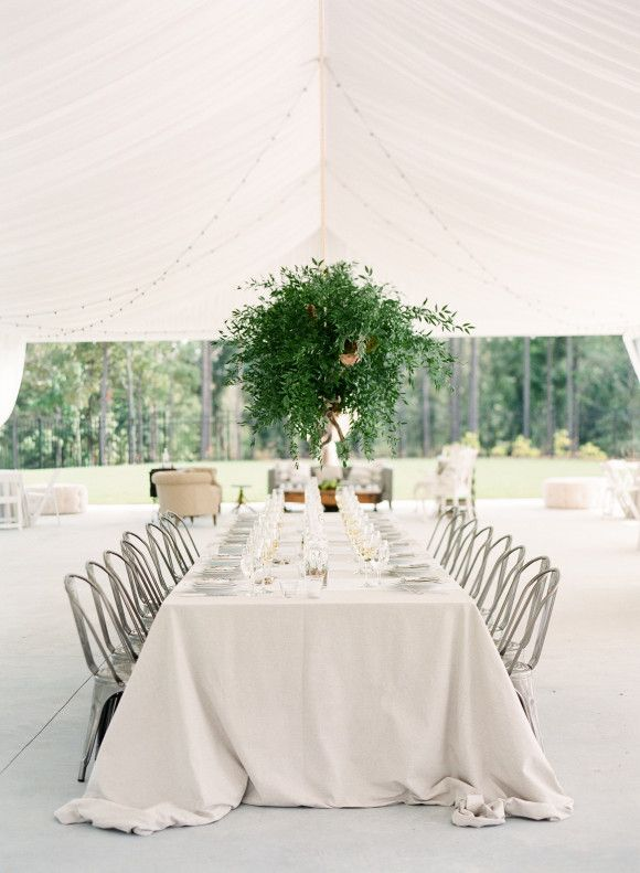 Beautiful white-washed tablescape featuring a tall, lush green arrangement. #wedding #decor