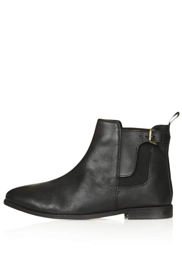 Black leather Chelsea boots with buckle detail.