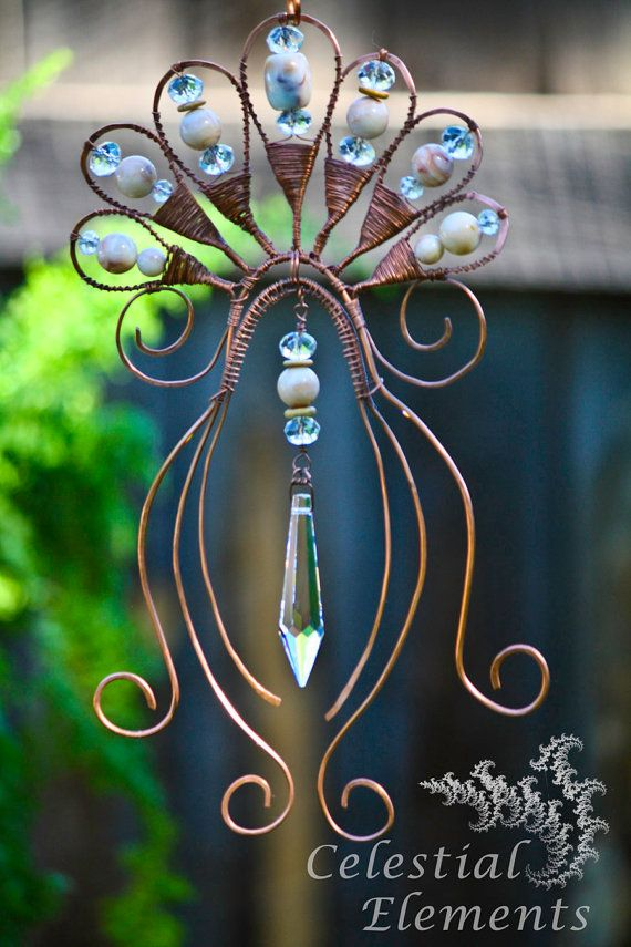 Sun Catcher or window art. Has copper wire bent the shape of a Lotus Flower. A large crystal is suspended in center. Orintal look. symbolic
