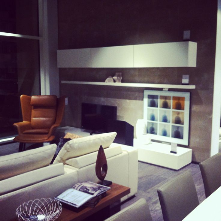 White volani wall units on a concrete wall. Tan leather and some wooden accessories prevent this being a cold look.