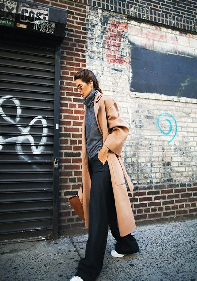 A turtleneck is worn with a camel coat, wide-leg pants, and sneakers