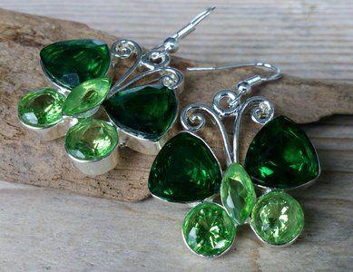 Zilverkeurige vlinder oorbellen met groene stenen.