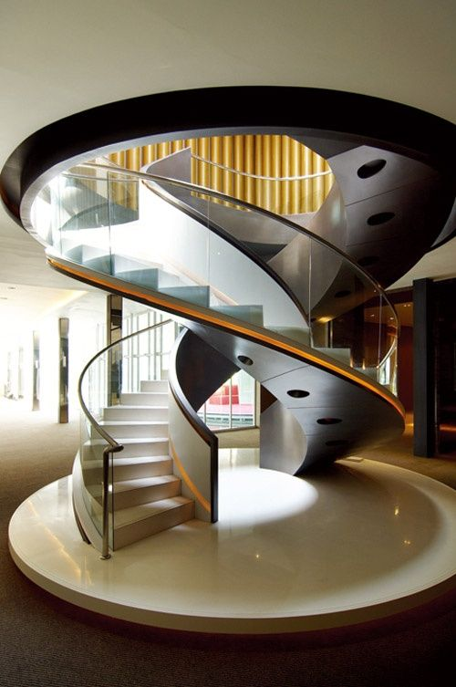 A pair of twin corkscrewing helical staircases with integrated lighting in the soffit and internal solid balustrade.