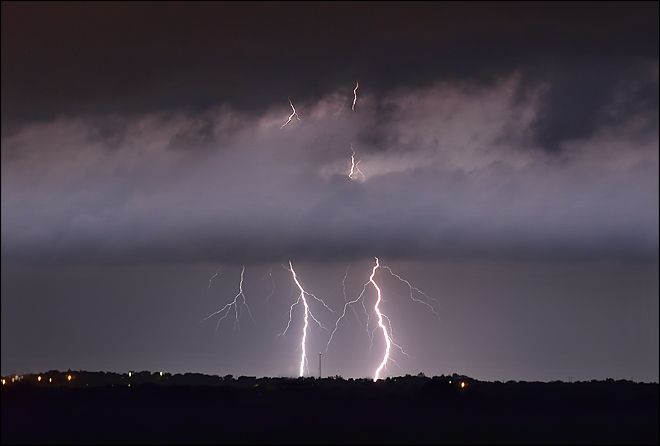 In this Wednesday, May 20, 2015 photo, lightning strikes between the towns of Krum and Sanger in Denton County, Texas, as a tornado warning was in effect for Sanger, Bolivar and Krum just after midnight. (Al Key/The Denton Record-Chronicle via AP)