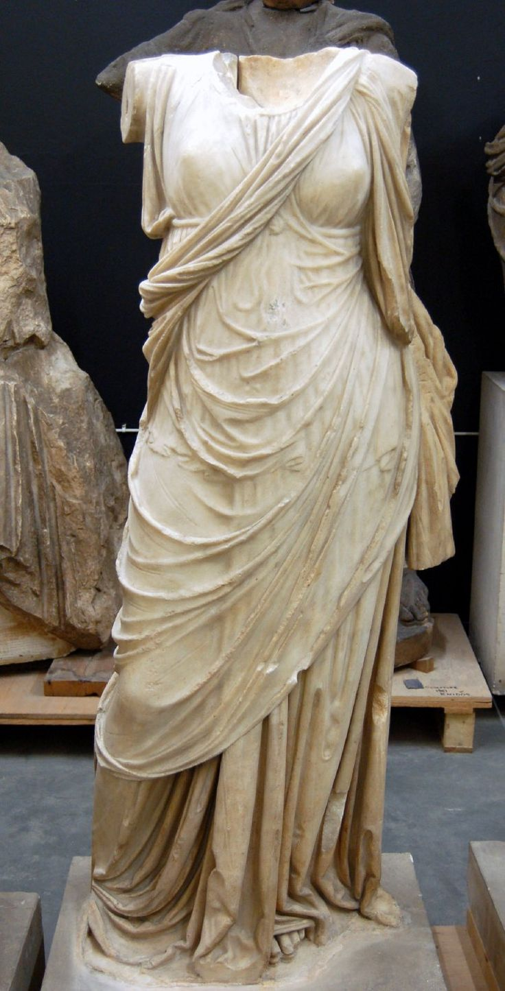 Marble statue of a draped woman.  She wears a flimsy chiton over which a himation is draped.  The folds of the under garment are carefully conceived.  The arms and head were separately made and are now missing.  A piece of drapery was separately made at the rear shwoing the overfall of the himation.