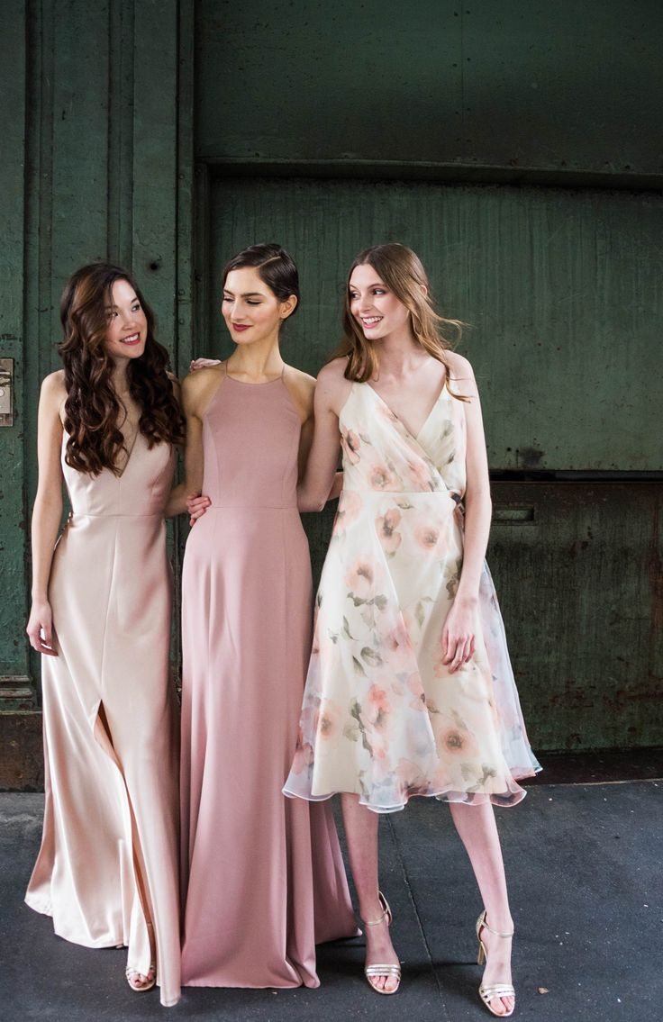 Jenny Yoo 2018 Bridesmaids, blush mismatched long and short bridal party styles for spring wedding. The glamorous Satin Back Crepe 'Corrine' dress features a plunging V halterneck and an eyecatching wrapped strap detail in the back. The luxe chiffon Kayla dress features a high halter neckline and straps hooked at the center back, with a long skirt and above the knee slit. The Sabrina dress features a surplice bodice with spaghetti straps and taffeta tea length skirt for a feminine…