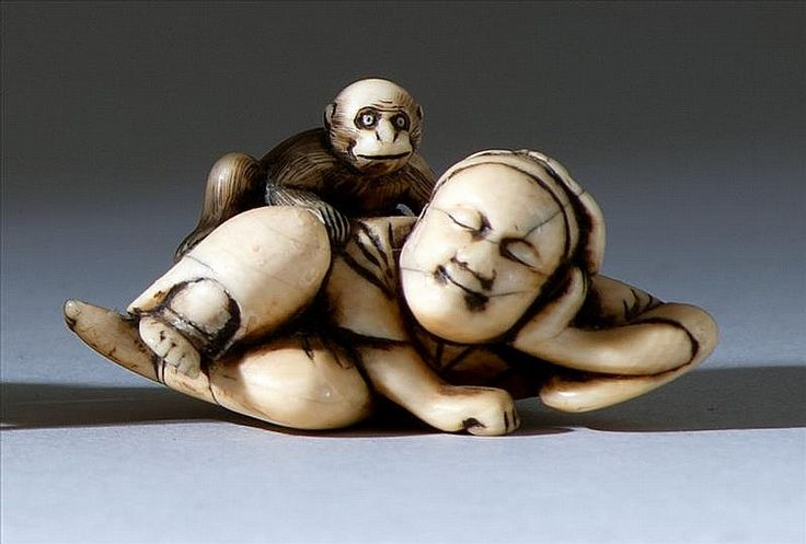 "IVORY NETSUKE 18th Century In the form of a sleeping man with a monkey stealing from his basket. Length 2"" (5 cm)."