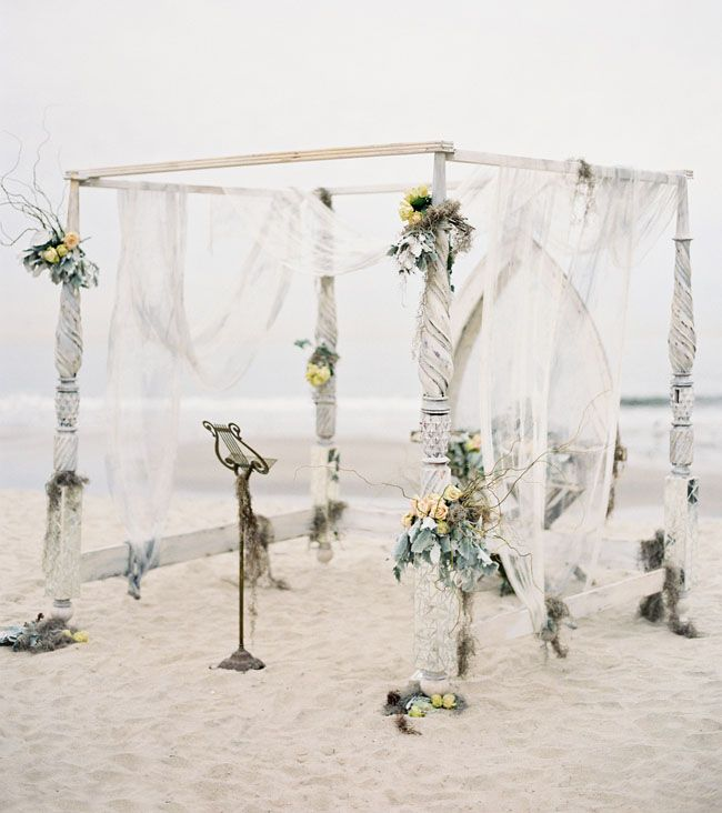 """""""We got married under an old vintage canopy bed that had been white washed and turned into a ceremony structure. I had even tiled pieces of mirrors to the legs of the bed to give it a glamorous edge and Studio Fiore twisted flowers into the structure and tables to give it that 'washed ashore' feel I was going for."""" How eerily gorgeous and unique?!"""