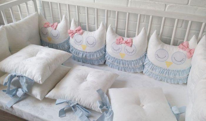 Белые бортики-подушки, украшенные голубыми лентами, розовыми бантами