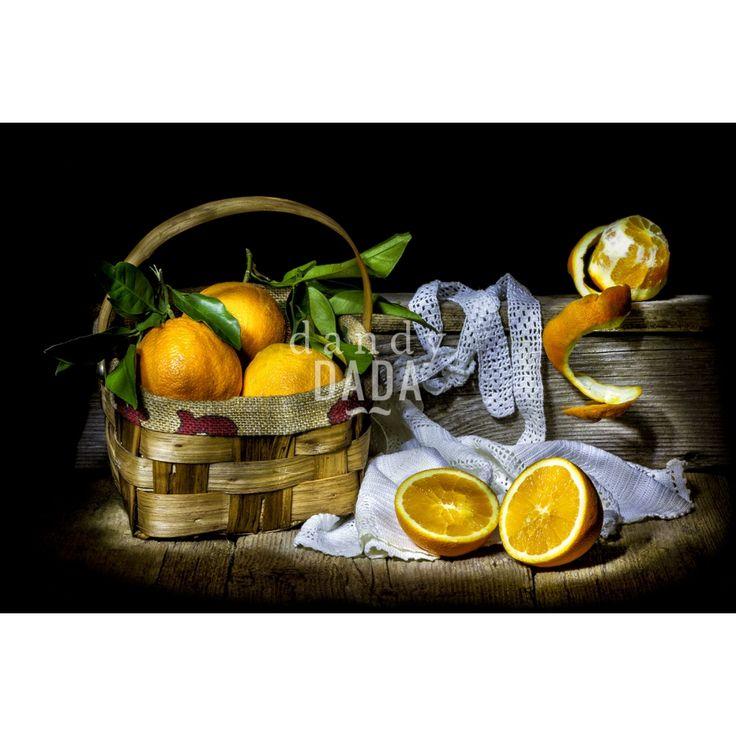 Arance con cestino di Manolo Tatti è un omaggio a Francisco de Zubaran. Come nelle nature morte del pittore spagnolo anche qui non vi è la ricerca spasmodica e ridondante di gustose pietanze ma, tutto è regolato dalla semplicità. Le forme purificate dalla luce cristallina, che penetra da sinistra, rispondono a uno stile controllato. La monumentalità dei frutti è addolcita dall'arabesco delle foglie verdi, dal soffice panneggio del centrino di pizzo e dal ricciolo della buccia in alto a…
