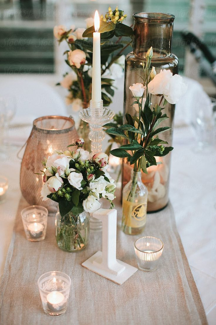 Neutral wedding reception tablescape with candles …