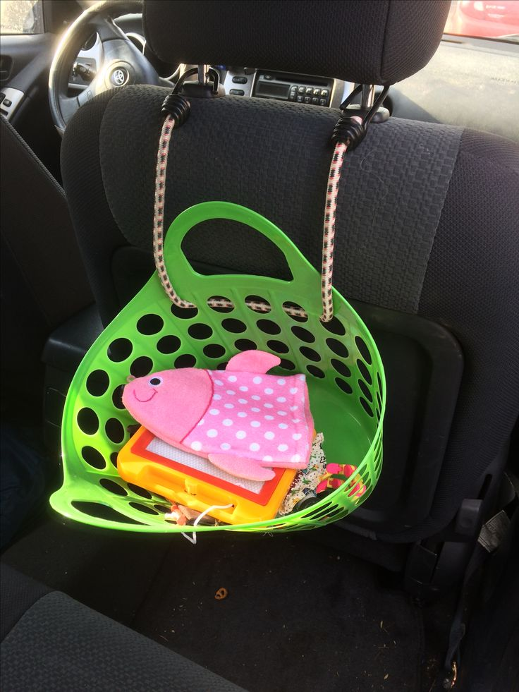 How to amuse a toddler in the car: Bungee cord a basket from the dollar store to the back of the passenger seat and fill with snack bags, puppets, dolls, games, and more. Remember to rotate the toys!