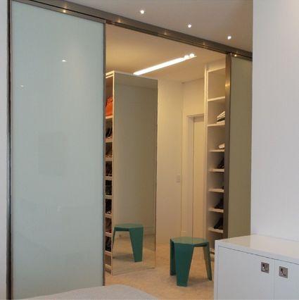 Closet com portas de correr em vidro da Ornare, projetado por @mariabrasilarquitetura