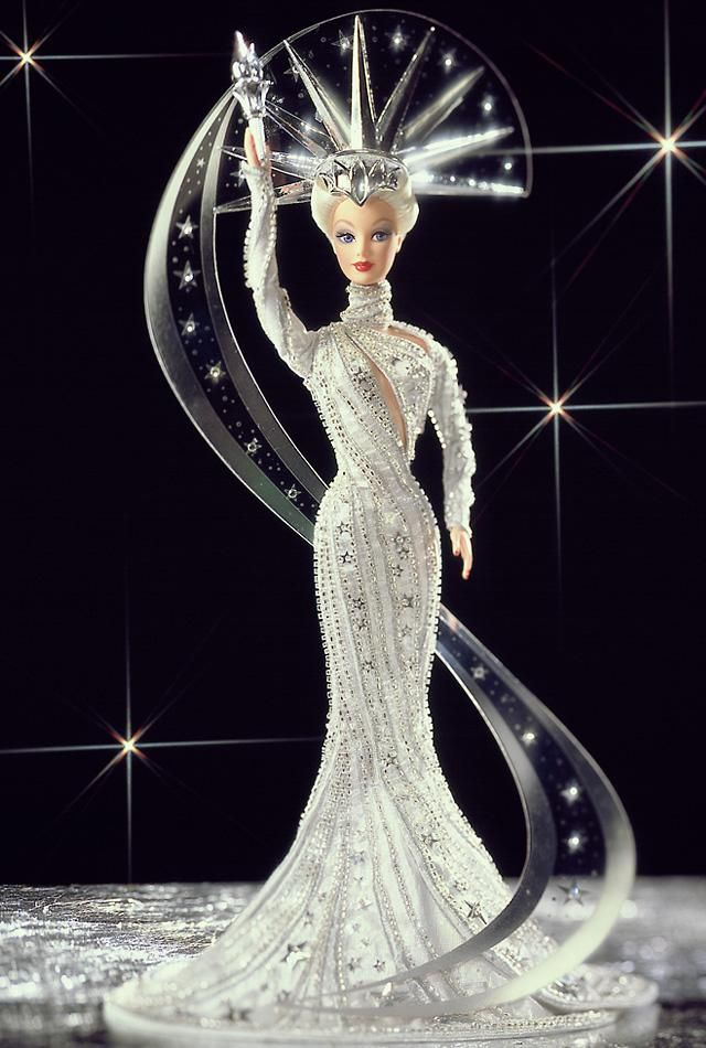 Bob Mackie's latest masterpiece commemorates a classic American landmark. Lady Liberty™ Barbie® is dressed in a fitted silver metallic gown with long sleeves + sweeping train. Silver embroidery, bugle beads + silver star sequins accent her lovely flowing gown. She wears an elaborate headpiece, the beginning of a clear sweep of sparkling rhinestones + stars that circle her length. She shines from head to toe. Barbie® & the Statue of Liberty, 2 symbols that stand for all things American!