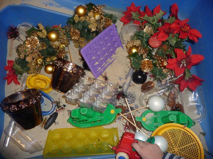 Map juf Ineke: sensomotoriek; de zandtafel gevuld met kerstdecoraties en zand, plantenpotjes ed. Kinderen kunnen kerststukjes maken.