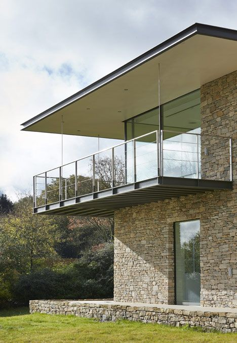 This house in the Oxfordshire countryside was designed by London studio The Manser Practice with a Cotswold stone facade and a cantilevered terrace overlooking the woods