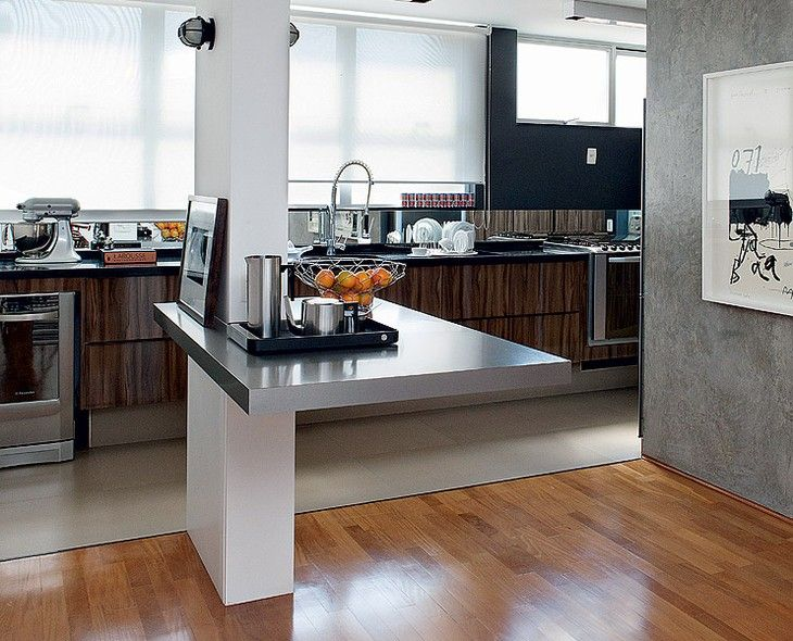 """Ao demolir a parede que separava sala e cozinha, restou uma coluna estrutural. O """"incômodo"""" foi aproveitado para criar uma mesa de apoio à cozinha, que o morador Chico Paese usa como bar quando recebe os amigos. Projeto do escritório Arqdonini"""
