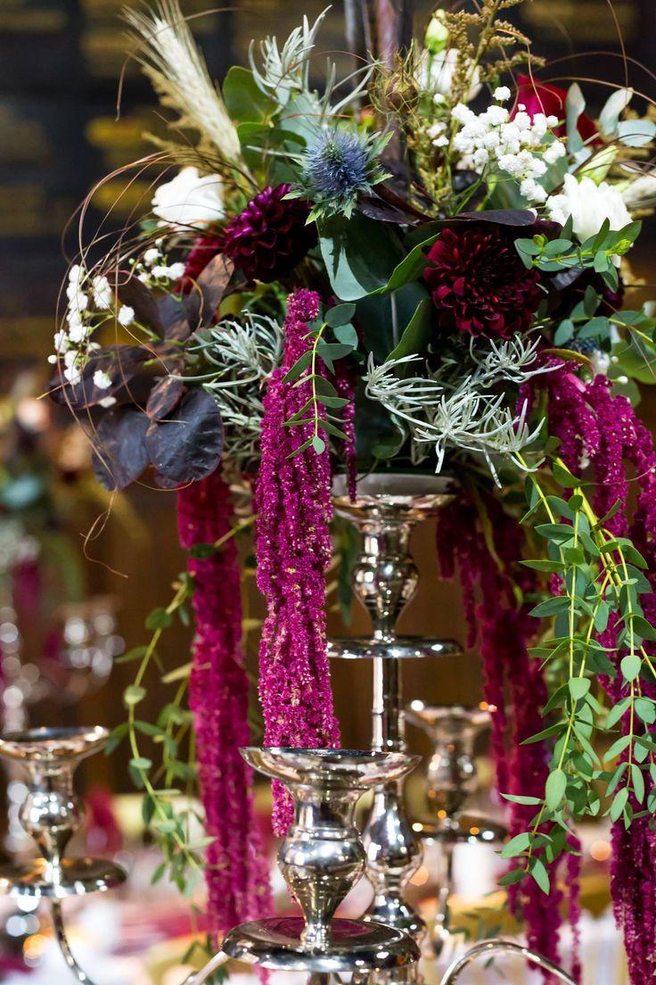 Dramatic floral candelabra arrangement using the petrol blue of the eryngium to contrast with the burgundy and white. Flowers by Honey Pot Flowers.  Photograph by Amy Bennett Photography