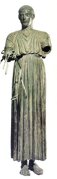 The Charioteer of Delphi and details of his Chiton, a version called xystis used by all chariot drivers during the race. It spans the whole body all the way to his ankles. It is fastened high at the waist with a plain belt. Two straps cross high at his upper back and round his shoulders keep the chiton fixed during the race.