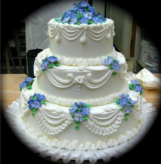 Incredible icing design on wedding cake. Blue forget me nots. Delphiniums. I want icing that drapes or swoops like this for my cake but instead of the gum paste forget me nots I just want real pink roses on the top. Moio's Bakery in Monroeville, PA near Pittsburgh.