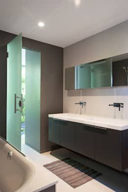 This bathroom is all about frosted glass and serious looking wood which is balanced by the glossy white fittings and the frameless mirror above the sink. Neutral soothing colors make this a welcoming space. Modern Houses by OPEN ARCHITECTES.