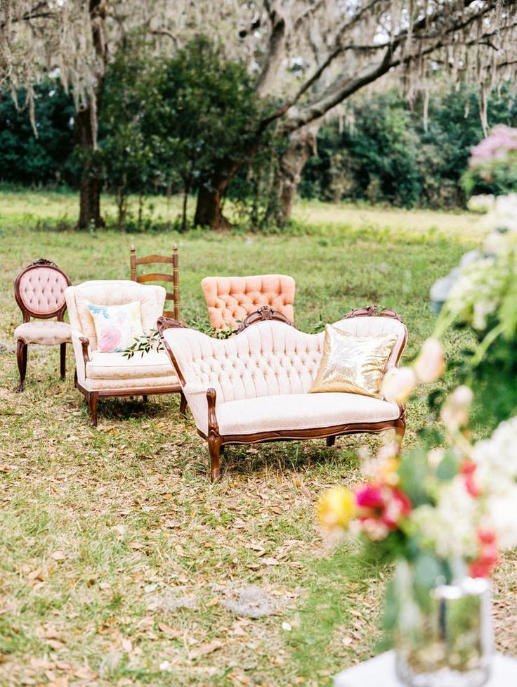 Vintage Outdoor Wedding Ceremony Under Oak Trees With Mis Matched Vintage Upholstered Chairs