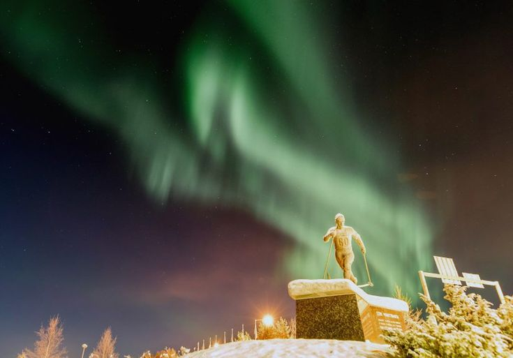 Northern lights and the statue of the Olympic winner Eero Mäntyranta at the center of Pello in Lapland