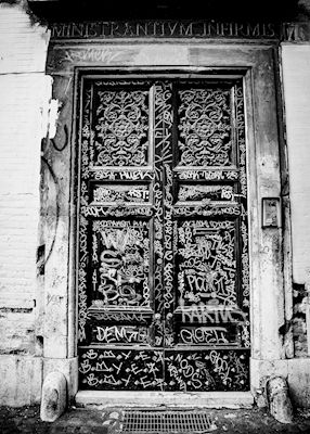 An old classical door in Rome covered in graffiti. Black and white photograph with high contrast by Marianne Brattberg. Available as poster and laminated picture at printler.com, the marketplace for photo art.