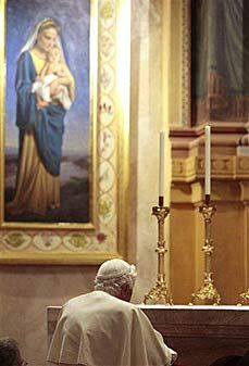 His Holiness Pope Benedict XVI kneeling in prayer before the main altar at the opening of Domus Australia, the painting of Our Lady of the Southern Cross visible in the background.