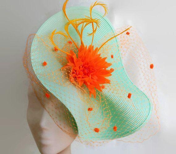Tocado turquesa y naranja. Base del tocado en tono verde agua decorado con velo spot, plumas y flor dalia naranja.  Es un tocado con colores vivos que